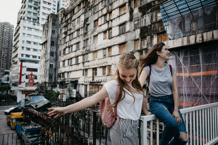 Smiling female friends against buildings in city