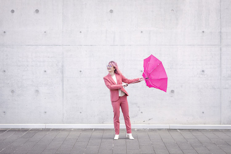 Woman holding pink umbrella standing on rainy day