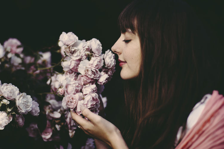 Close-Up Of Young Woman Smelling Flowers