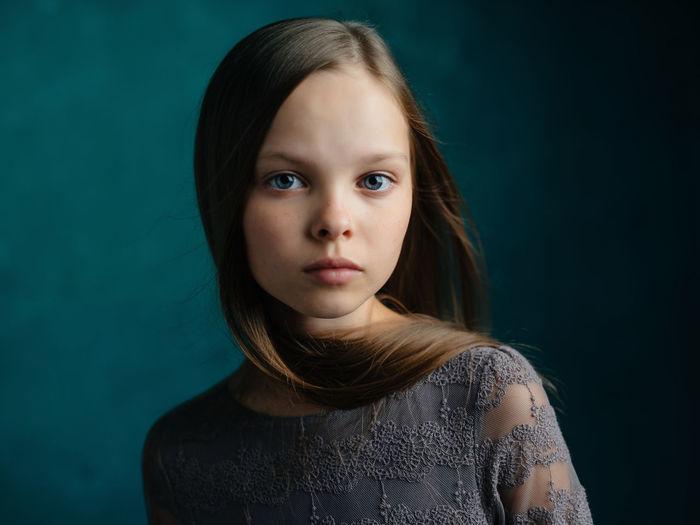 Portrait of teenage girl against black background