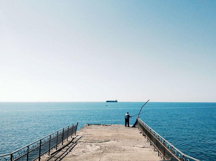 Rear view of man fishing on pier against sea