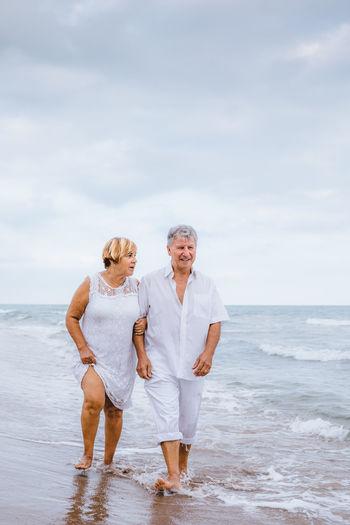 Romantic Senior Couple Walking At Beach Against Sky