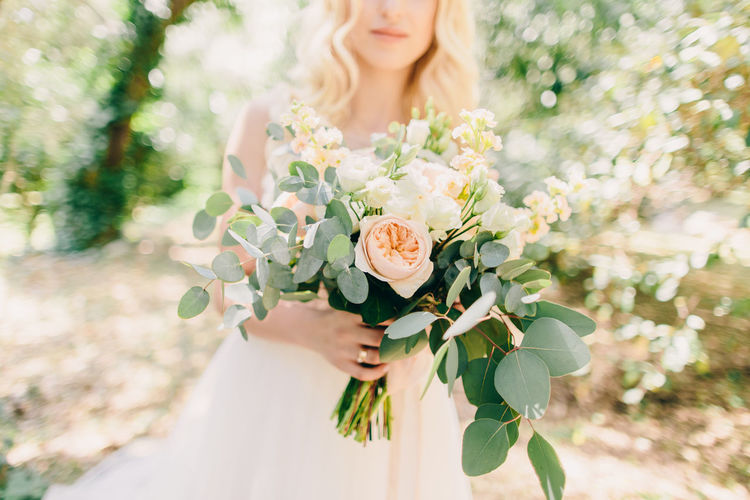 Midsection Of Bride Holding Flower Bouquet While Standing At Park
