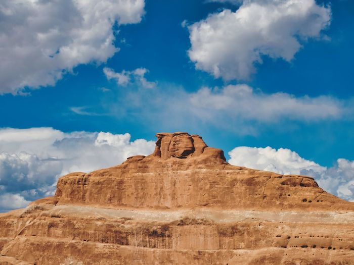Low angle view of rock formations against cloudy sky