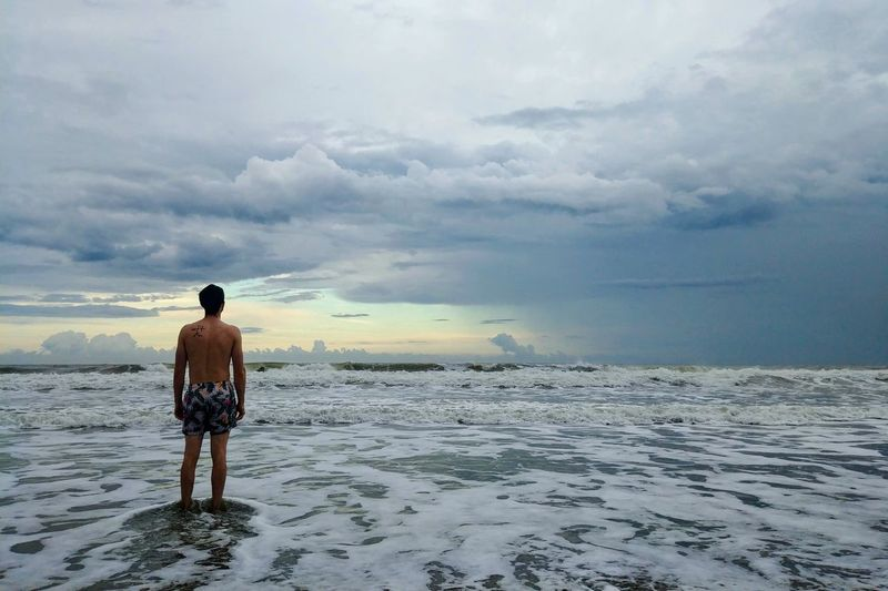 Rear view of shirtless young man standing at beach