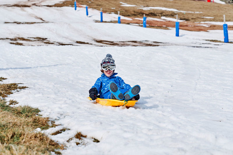Girl playing on snow covered land