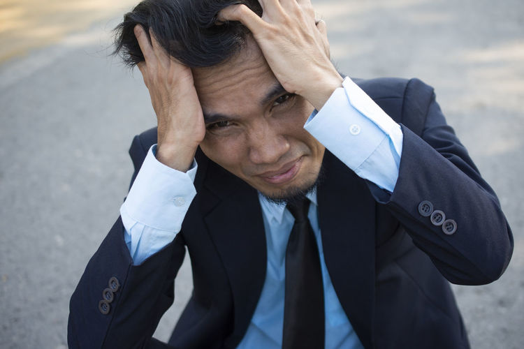 High angle portrait of stressed businessman with head in hands sitting on road