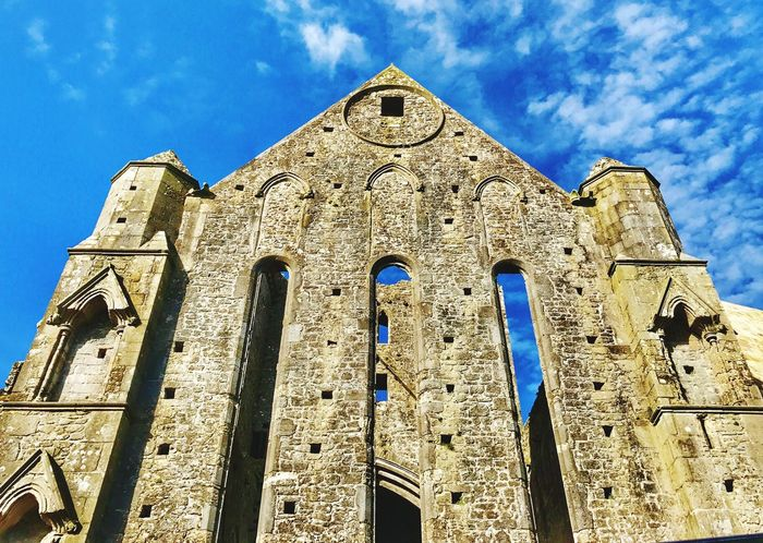 RockOfCashel-StandingTall Low Angle View Architecture Sky Building Exterior Built Structure Religion Blue Place Of Worship No People Day Outdoors Spirituality Rose Window Ireland Tipperary Rock Of Cashel