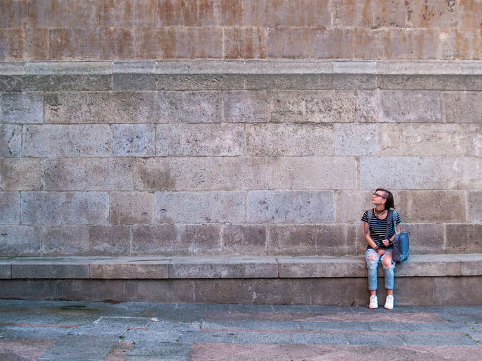 Full length of teenage girl sitting against wall