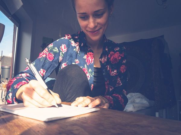Young Adult One Person Writing Table Young Women Real People Sitting Indoors  Desk Smiling Lifestyles Happy People Shopping List Day Adult People Wooden Desk Writing Pad NotePad Writing Instrument Take A Note Writer Creative Notes