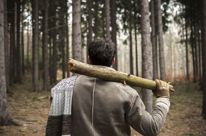 Rear view of young man holding log while standing in forest