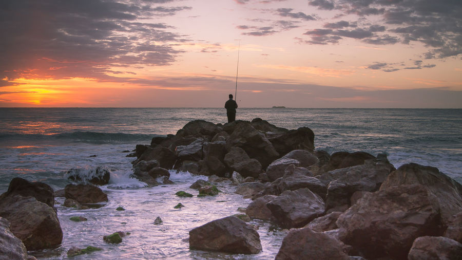 Man standing on rock at beach during sunset