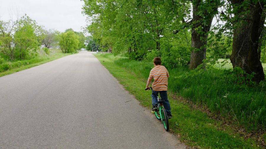 Rear view of boy riding bike