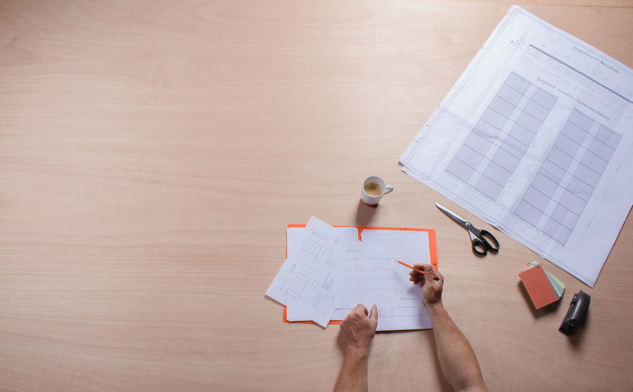 Table view male hands, planning, building footprint Architecture Binder Briefcase Cup Of Coffee Desktop Documents File Folder Footprint Building Ground Plot Holding Pencils In A Hand Human Hands Making Plans Male Hands Office Paper Pencil Scissors Table View Topview Wood Work Working Working Desk Writing