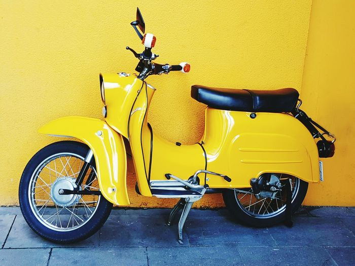Scooter against yellow wall