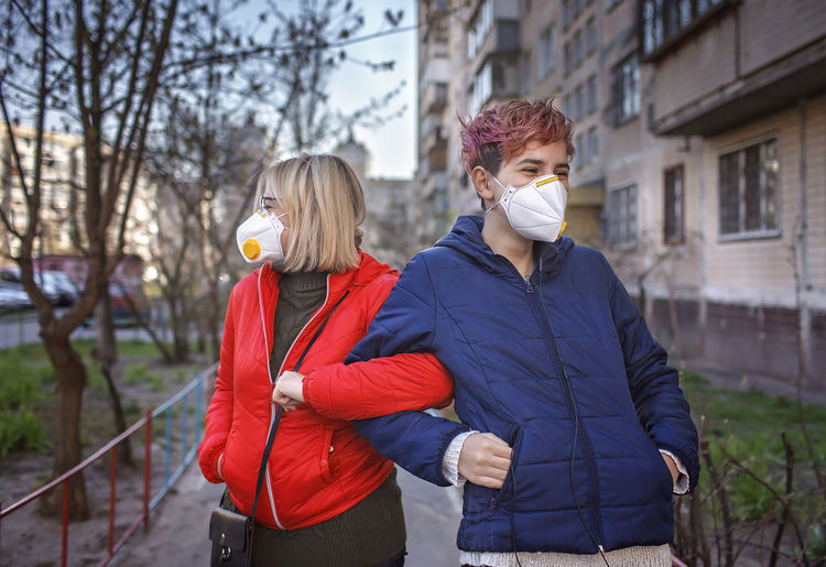 Mother and son wearing mask standing outdoors