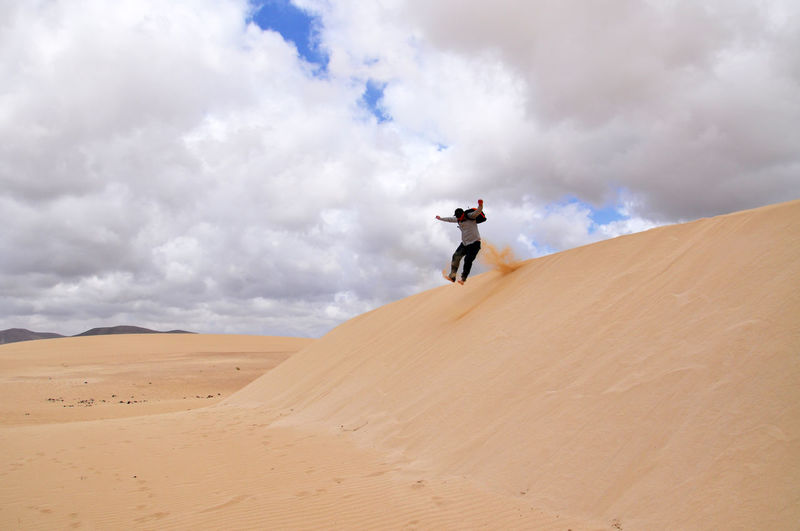 Low Angle View Of Man Jumping At Desert Against Cloudy Sky