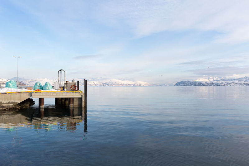 Landing stage for fishing industry in Northern Norway Architecture Beauty In Nature Cloud - Sky Cold Temperature Commercial Dock Fishing Industry Fjord Harbor Jetty Landscape Mountain Nature Pier Reflection Remote Scenics Sea Sky Smooth Snow Sunny Tranquility Water Waterfront Winter