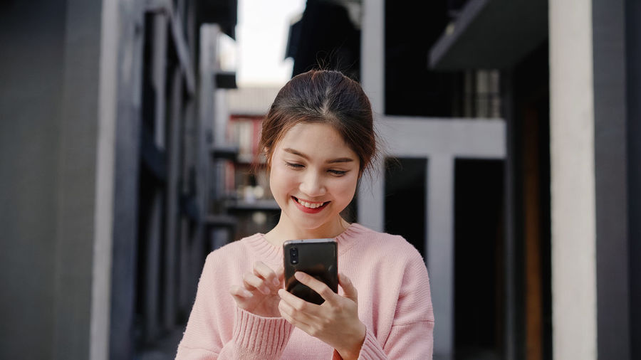 Smiling woman using mobile phone in city