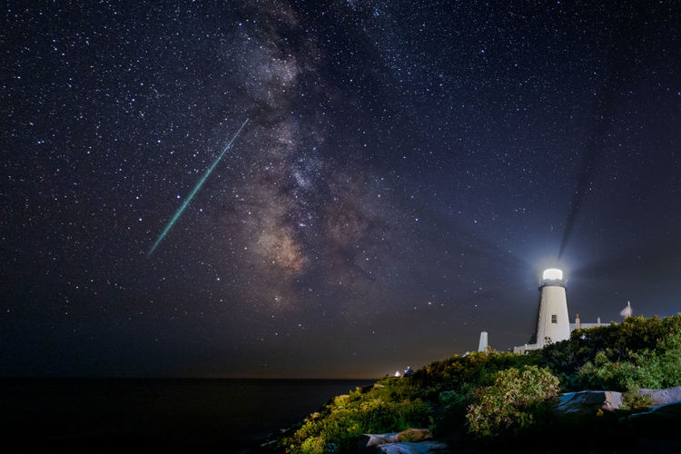 The milkyway and a meteor lights up the night sky off the coast at the pemaquid point lighthouse.