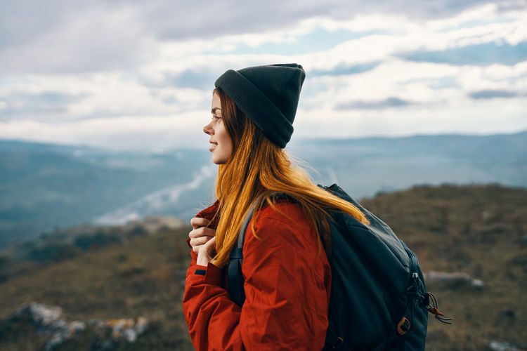 Side view of young woman looking away against mountain