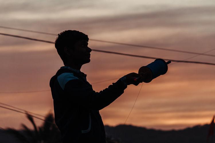 Boy flying kite during evening