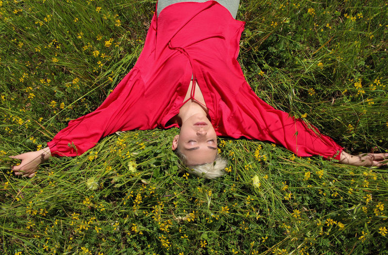 High Angle View Of Young Woman Lying On Grass