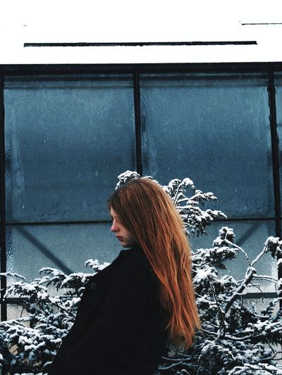 Side view of woman standing against window during winter