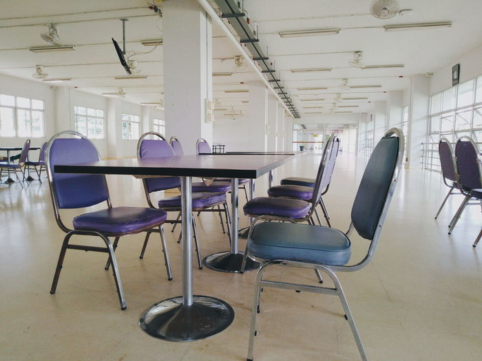 Empty chairs and tables in building