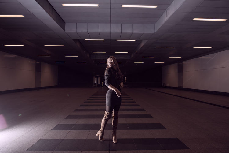 Full Length Of Woman Standing In Illuminated Subway