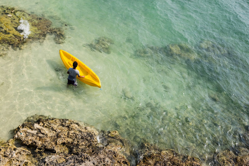 High Angle View Of Man With Kayak In Sea