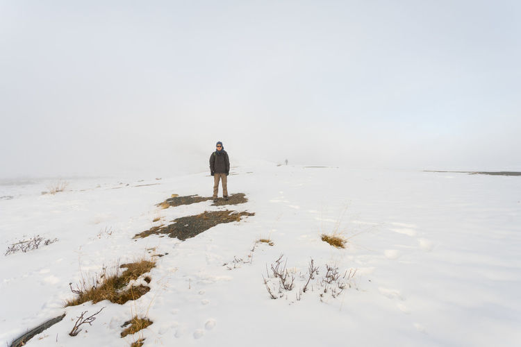 Rear view of man on shore against sky during winter