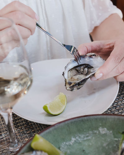 Food And Drink Human Hand Food Hand Holding Real People Freshness One Person Healthy Eating Citrus Fruit Human Body Part Kitchen Utensil Fruit Lemon Lifestyles Eating Utensil Table Refreshment Household Equipment Glass Preparing Food Oyster