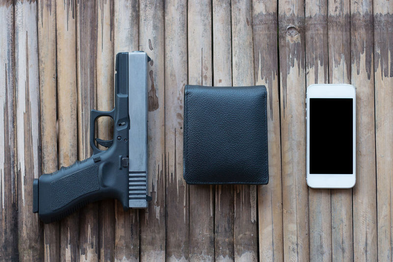 Gun pistol with Leather wallet and Smartphone on wooden background Background Bamboo Black Bullet Closeup Concept Crime Criminal Dangerous Dark Gun Handgun Hunter Isolated Leather Metal Mobile Modern Money Murder Object Old Pattern Phone Pistol Police Protection Shot Smartphone Steel Table Top View Violence Wallet Weapon White Wood Wooden Smart Phone Choice Equipment Mobile Phone Still Life Connection