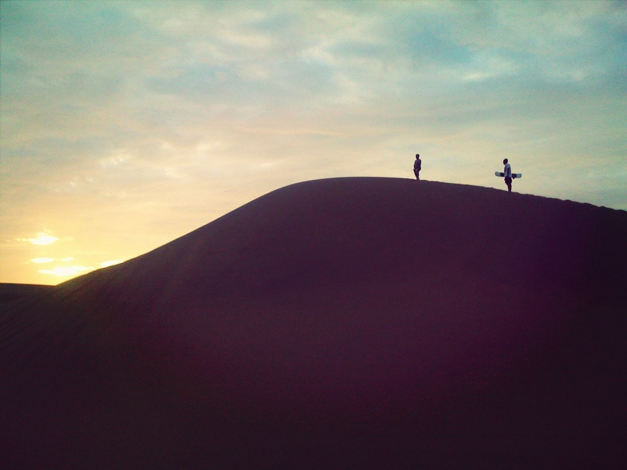 Side view of two silhouette people on landscape against the sky