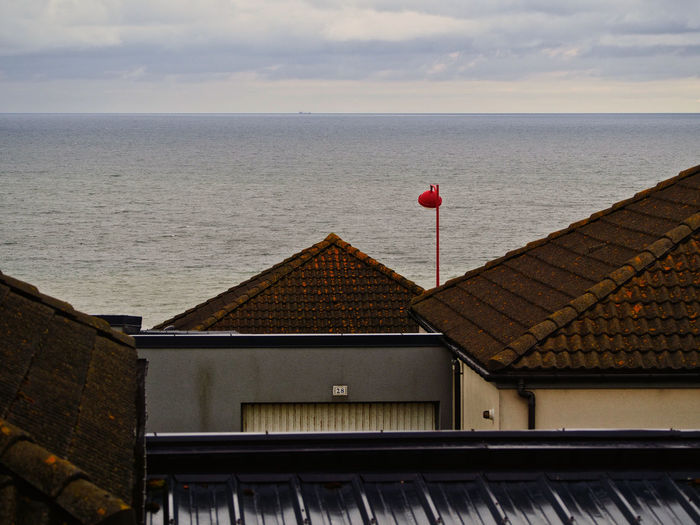 Red House By Sea Against Sky