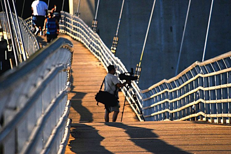 Photographer photographing through camera while standing on bridge