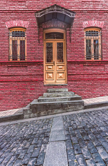 Behind a closed door City Colors Georgia Taking Photos Tbilisi Architecture Building Exterior Built Structure Cobblestone Day Door No People Old Outdoors Red Street Streetphotography Travel Destinations Window