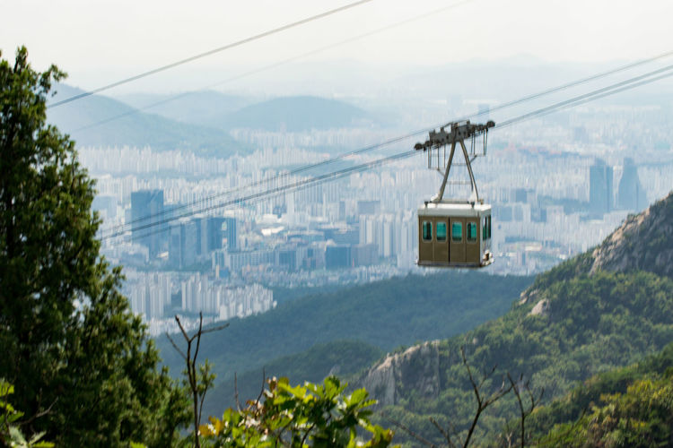 Overhead cable car over mountains against sky