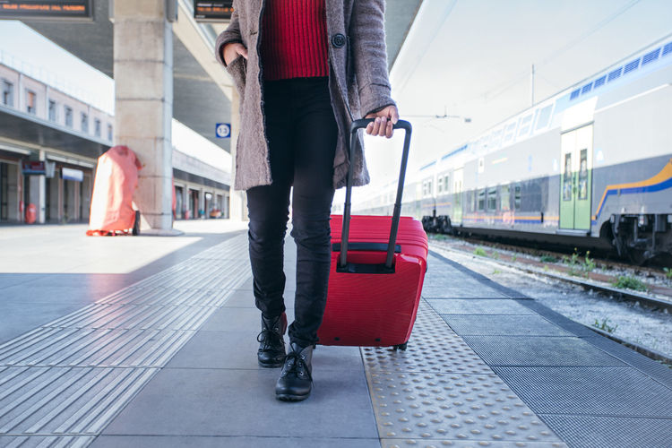 Low section of woman walking on railroad station platform