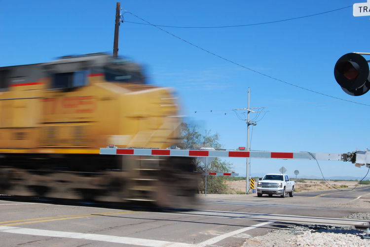 Picacho, AZ, USA - October 18, 2014: A speed blur of a locomotive passing through a railroad crossing. Taken October 18, 2014 Blue Blurred Motion City Street Day Diesel Editorial Photography Freight Trains Gates Industry Land Vehicle Locomotive Engine Mode Of Transport Motion Blur No People Outdoors Power Line  Railroad Railroad Tracks Road Rr Sky Stoplight The Way Forward Transportation Vehicle