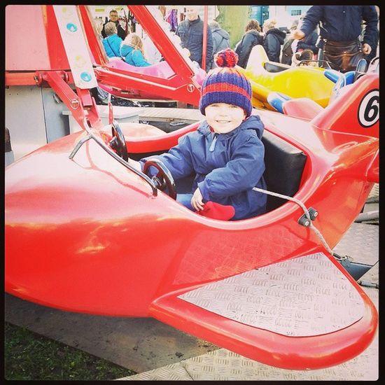Harrogate Christmas Market. Child Toddler  Happy Fun Plane Ride Red Bobblehat