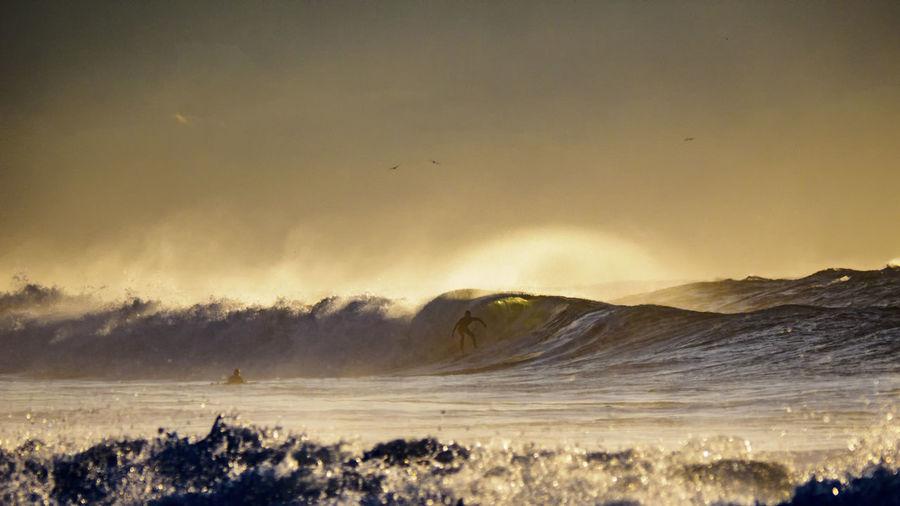 Idyllic view of splashing sea waves against sky
