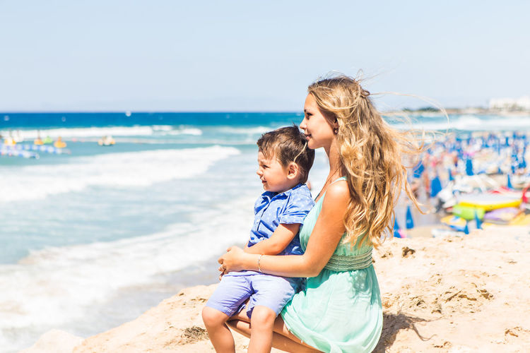Happy friends enjoying at beach against sea