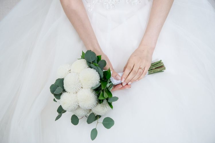 Bouquet Bride Bridegroom Celebration Celebration Event Ceremony Flower Groom Holding Human Body Part Human Hand Indoors  Life Events Love Married Midsection New Life One Person Real People Wedding Wedding Ceremony Wedding Dress White Color Wife Women