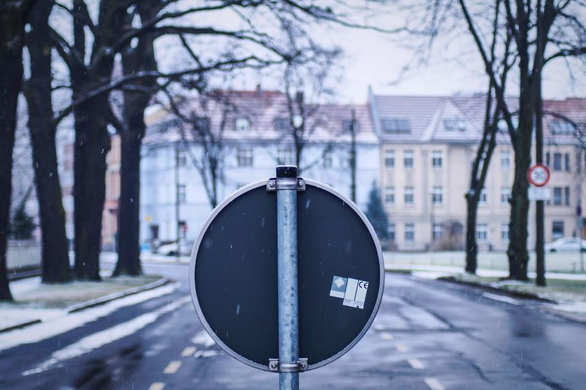 Traffic sign while snow ❄️ Wanderlust Streetphotography Street Tree Focus On Foreground Architecture Built Structure Building Exterior City Day Outdoors Close-up Road Sign No People Bare Tree Branch Clock Nature Cityscape Shades Of Winter