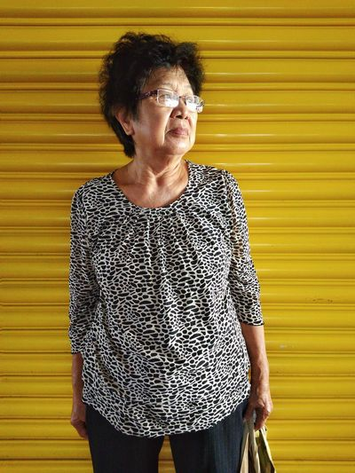 Mature Woman Standing Against Yellow Wall