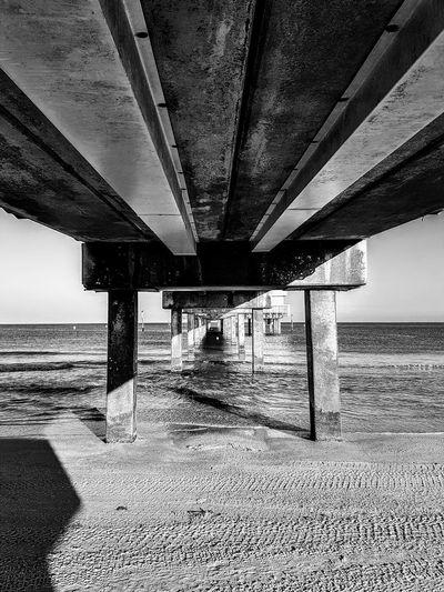 Interior of pier over sea against sky