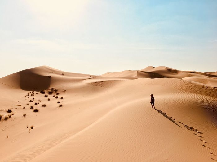 Rear view of boy walking in sand dune during sunny day