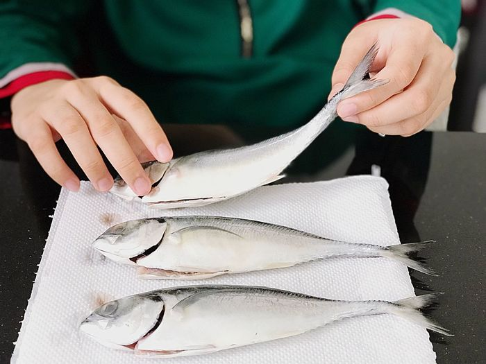 Midsection of person preparing fish at table